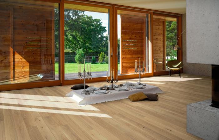 salón bonito decorado en beige y gris, suelo vinílico color claro, decoración con candelabros en estilo vintage