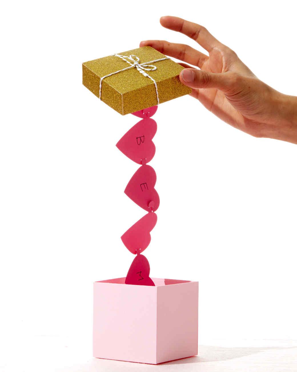 caja sorpresa para el día de san valentín, caja de cartón con guirnalda de corazones de papel, regalos san valentin hechos a mano
