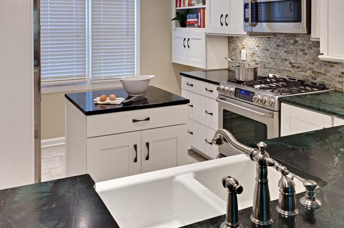 cocina funcional decorada en blanco y beige, encimeras de mármol, cocina con pequeña isla