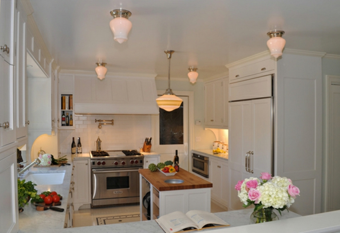 espacios decorados con mucho encanto, cocina blanca con muebles de diseño e isla con encimera de madera