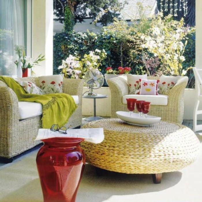 balcones pequeños con muebles de mimbre, decoración de cojines con estampados florales, grande jarrón de cristal color rojo