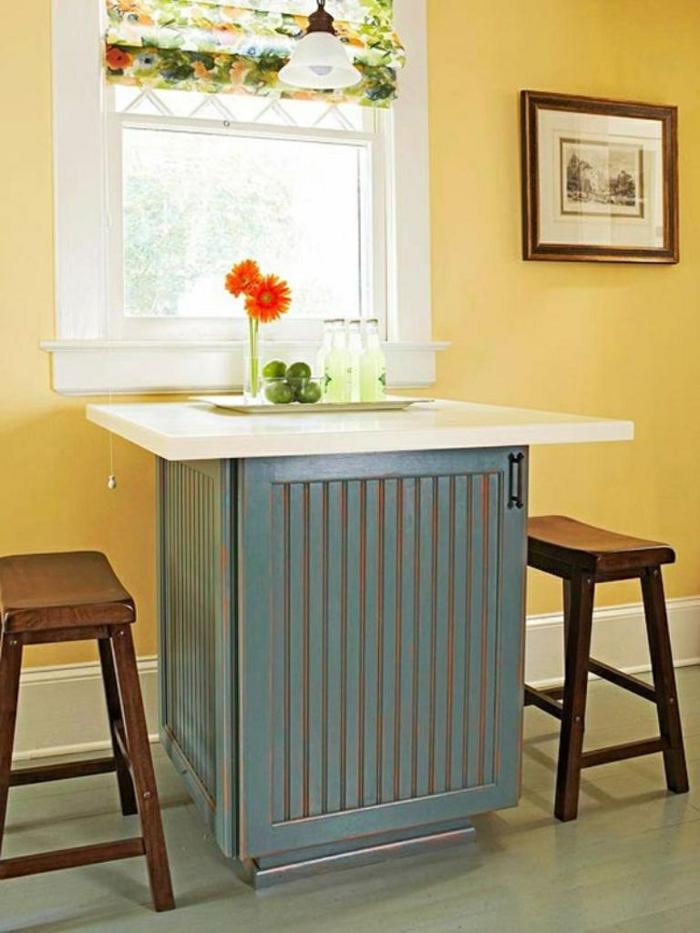 cocinas pequeñas con isla, paredes en color amarillo, isla con encimera blanca y sillas de madera