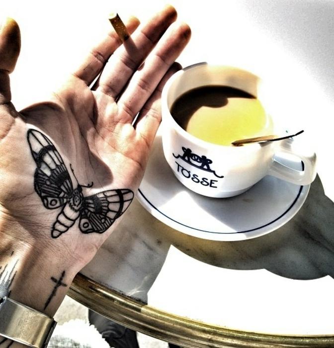 tatuaje en la mano con una mariposa negra, ideas de tatuajes de mariposas en bonitas imagines
