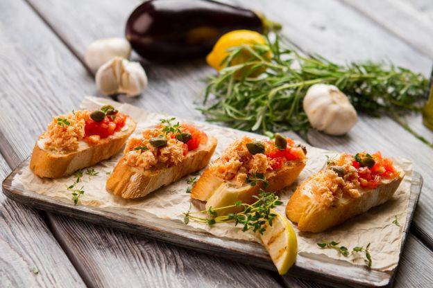 tostadas con atún, tomates y aceitunas, originales propuestas sobre como hacer canapes en fotos