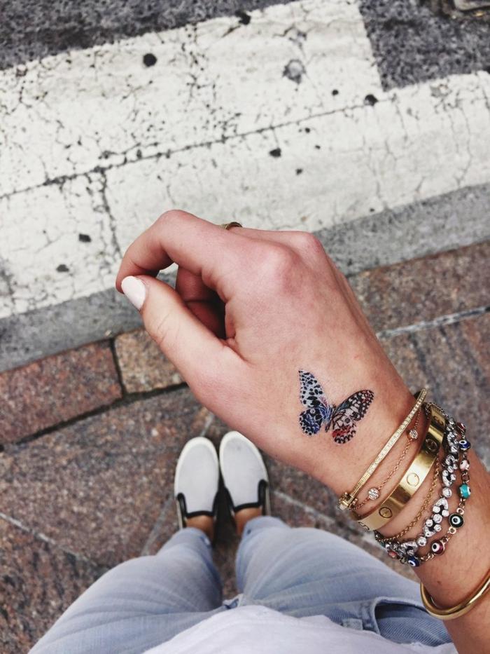 tatuaje en la mano, bonita mariposa en colores con pequeños detalles, tatuajes de mariposas en imagines