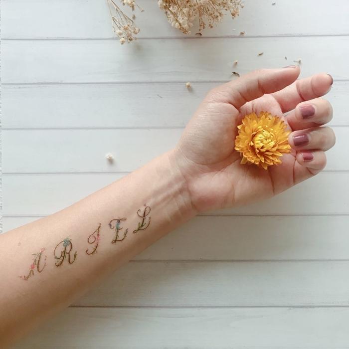 preciosos diseños de tatuajes mujer en el antebrazo, tatuaje adhesivo con letras y motivos florales