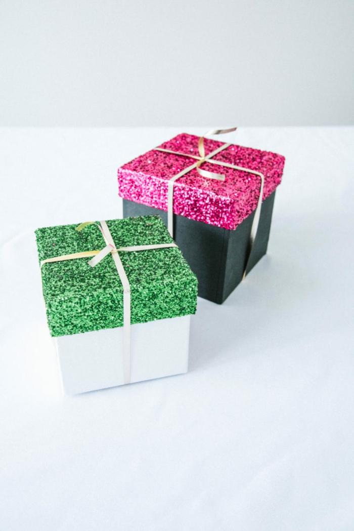 dos cajas para regalos con tapas decoradas con purpurina en verde y rosado y cintas en dorado