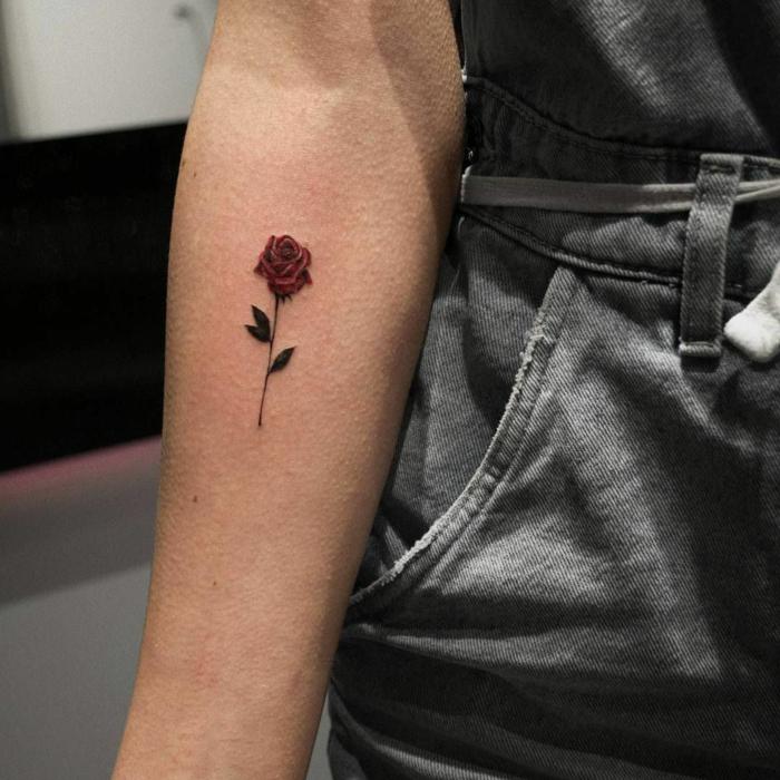 adorable tatuaje mujer en el antebrazo, pequeña rosa en estilo minimalista color rojo tatuada en el antebrazo