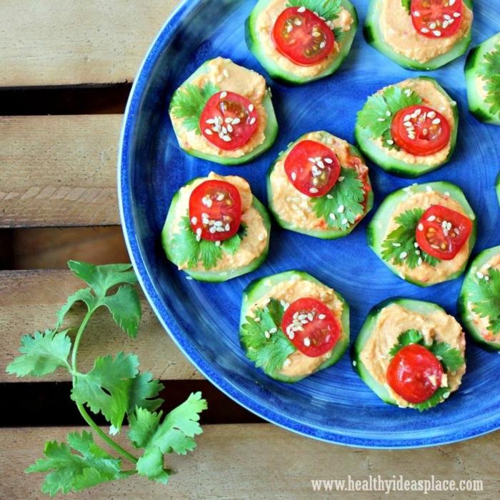 canapes faciles y super rápidos de hacer, rodajas de pepinos con hummus, perejil, cherry tomates y semillas de sésamo