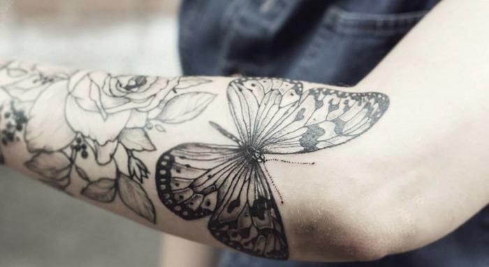 fotos de tatuajes en el antebrazo con mariposa y flores, mariposa negra y rosas tatuadas en el antebrazo