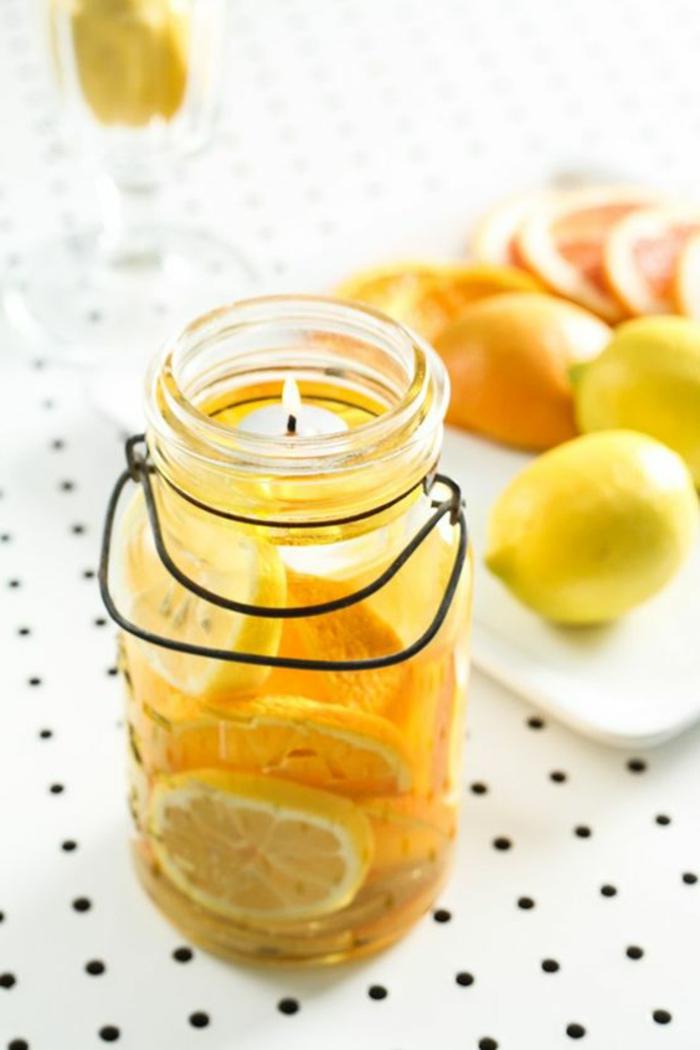 preciosas propuestas sobre como hacer velas caseras paso a paso, frascos de cristal llenos de velas y naranjas