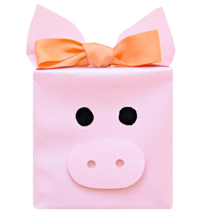 ejemplos de cajas para regalos originales, caja en color rosado en forma de cerdo con lazo color naranja