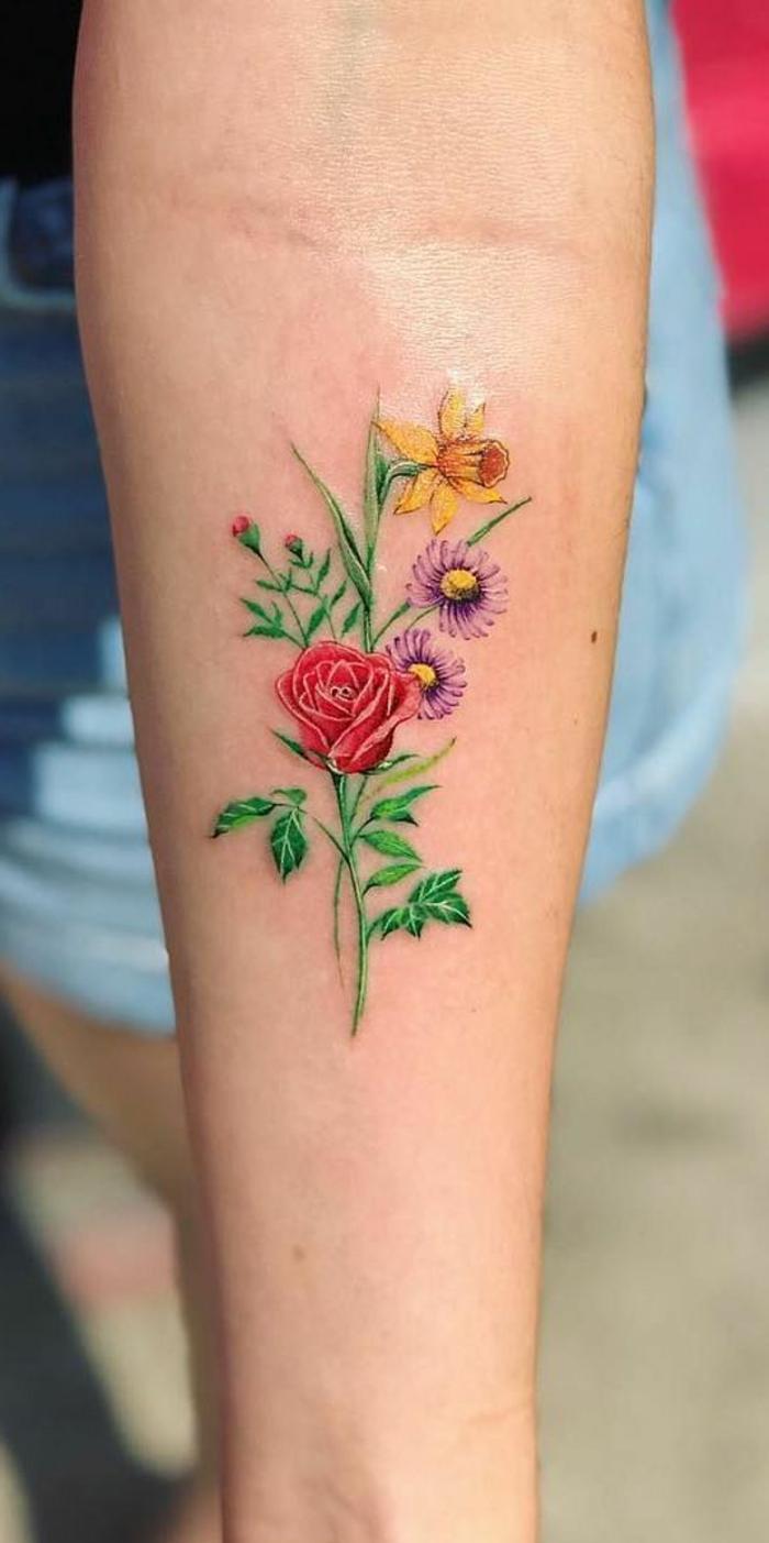 rosas de colores tatuadas en el antebrazo, diseños de tatuajes con fuerte significado, tattoos con flores