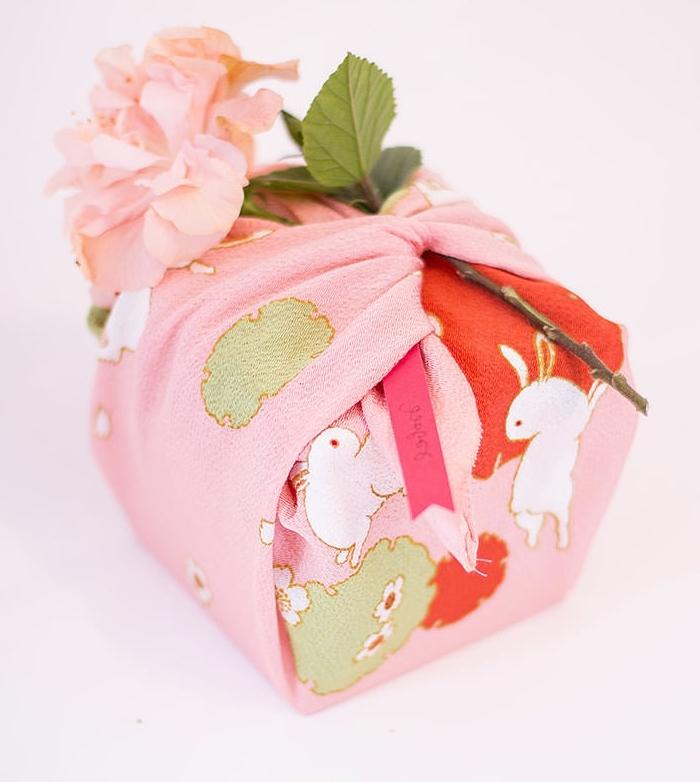 regalos bonitos envueltos en tela, pequeño detalle en colores pastel, caja de regalos con una flor