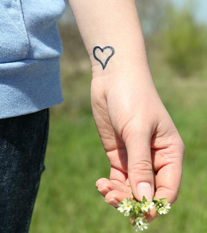 tatuaje en la muñeca mujer, pequeño corazón dibujado en la muñeca con rotulador negro permanente
