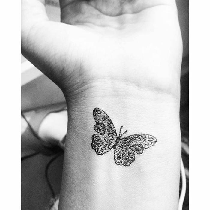 ejemplos de tatuajes en la muñeca con mariposa, tattoo pequeño tinta negra, pequeño detalle en la muñeca