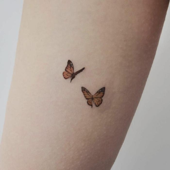 dos pequeñas mariposas color naranja tatuados en el antebrazo, tatuajes bonitos en fotos