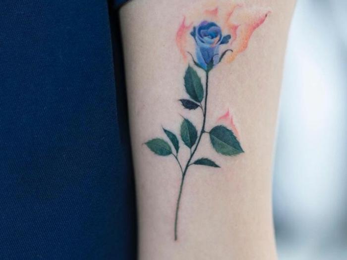 preciosa rosa en color azul tatuada en el brazo, tatuajes simbólicos en el brazo y antebrazo