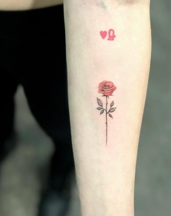 pequeño detalle en color rojo tatuado en el antebrazo, tatuajes con un fuerte significado, tattoos con rosas para hombres y mujeres