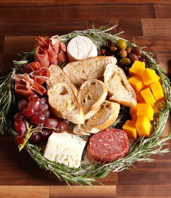 cesta con tapas ricas y originale,s tostadas, trozos de queso amarillo, chorizo, uvas y aceitunas
