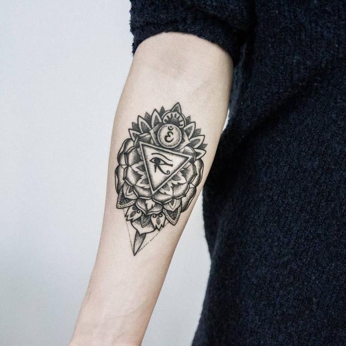 bonito y complejo diseño de tattoo geometrico con triángulos y elementos florales, ejemplos de tattoo antebrazo mujer
