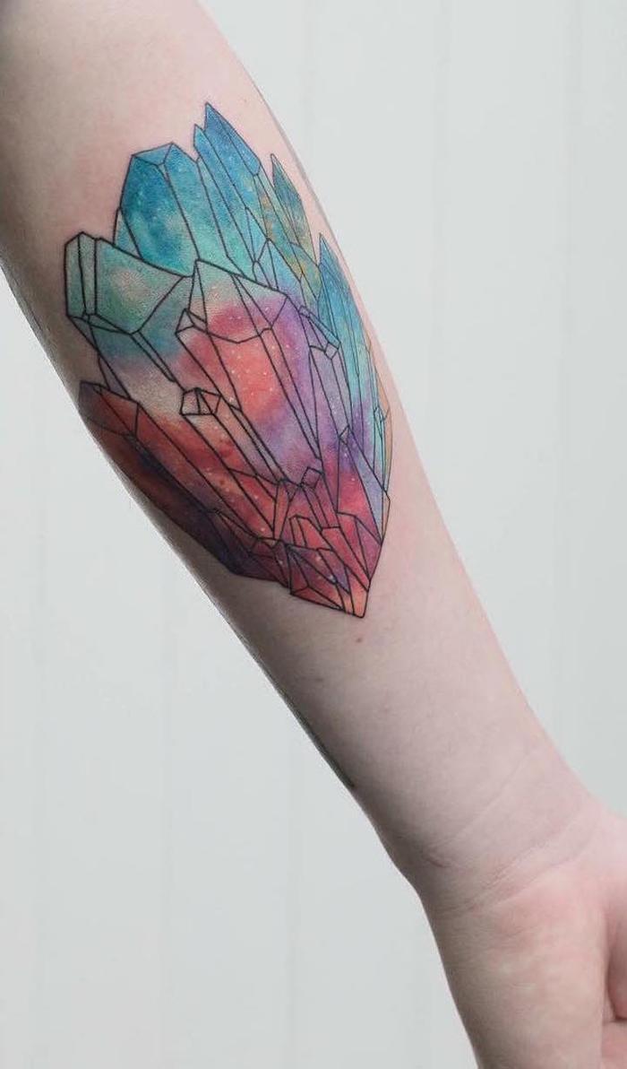 colorido tatuaje con acuarelas, tatuaje de cristales en el antebrazo, tattoo en azul y rojo