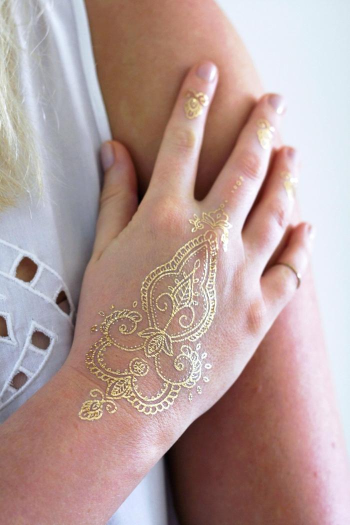 diseños bonitos de tatuajes con henna, mujer con mano tatuada con henna color dorado