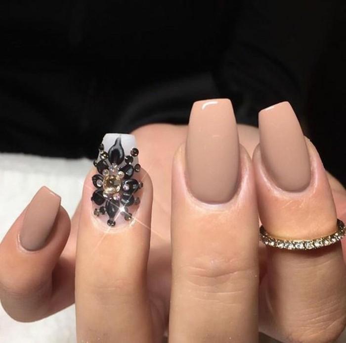 uñas largas de forma cuadrada pintadas en beige con bonita decoración de cristales negros en forma de flor