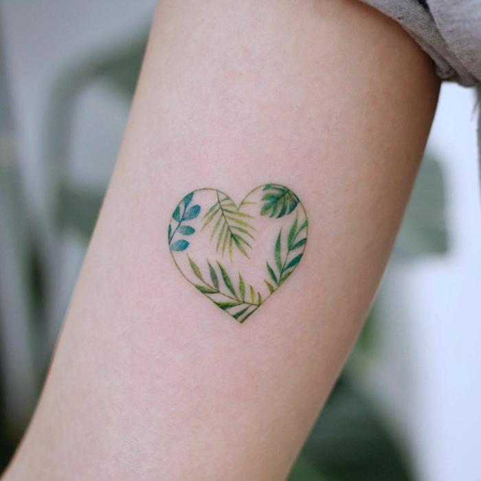 tattoo en el brazo de corazón pequeño con elementos botánicos, tatuajes para hacerse en pareja