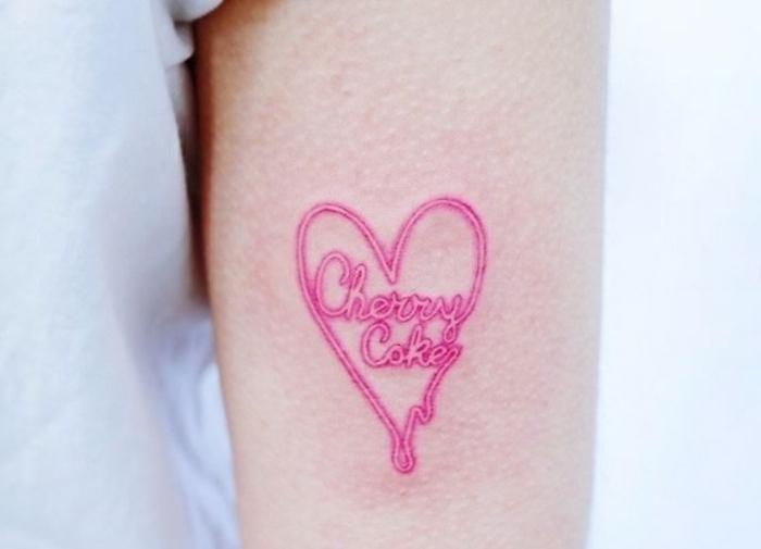 tatuajes de corazones super bonitos, diseños de tatuajes mujer en el brazo, precioso corazón en color rosado con letras