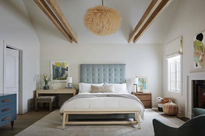 dormitorios matrimonio grandes, cama doble con cabecero en capitoné, paredes en color beige y vigas de madera en el techo