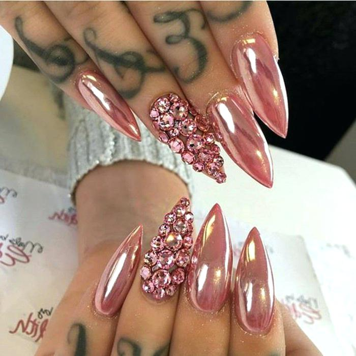 diseños de uñas exclusivos, uñas largas de forma stiletto pintadas en rosado metalizado, uñas decoradas con piedras