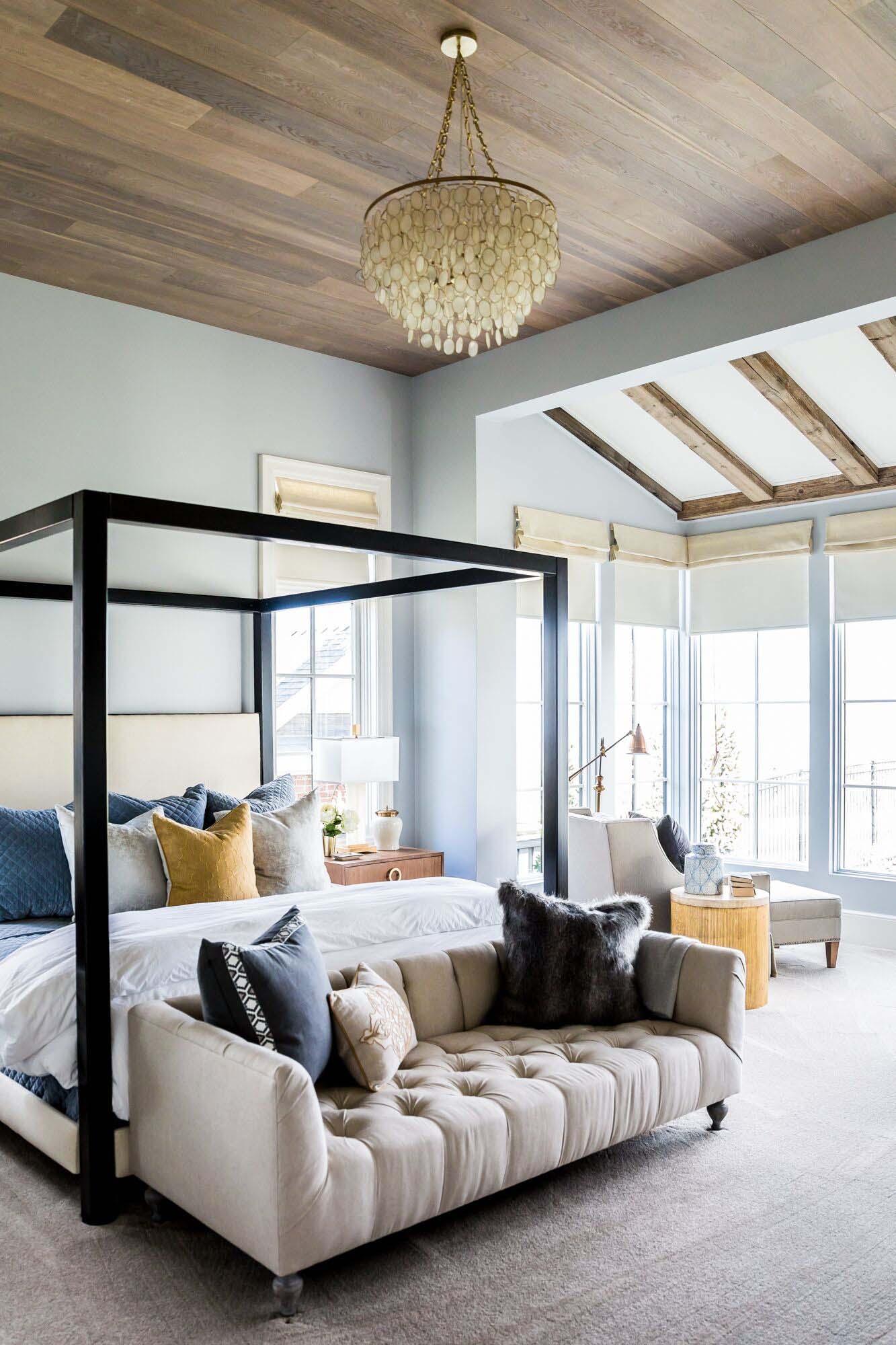 cama doble con marco moderno, habitación con paredes en azul claro, techo de parquet, lámpara original