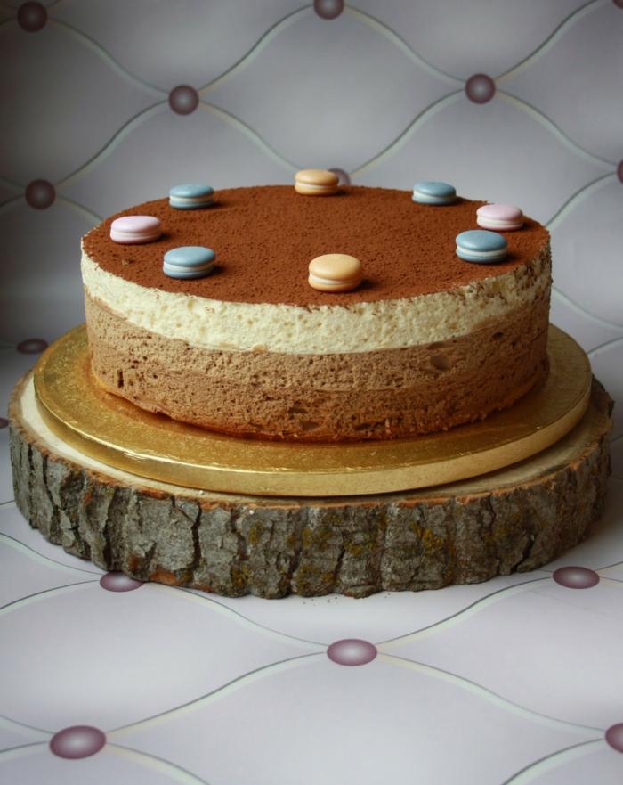 preciosa tarta mousse adornada con macarons pequeños en colores pastel y cocoa en polvo