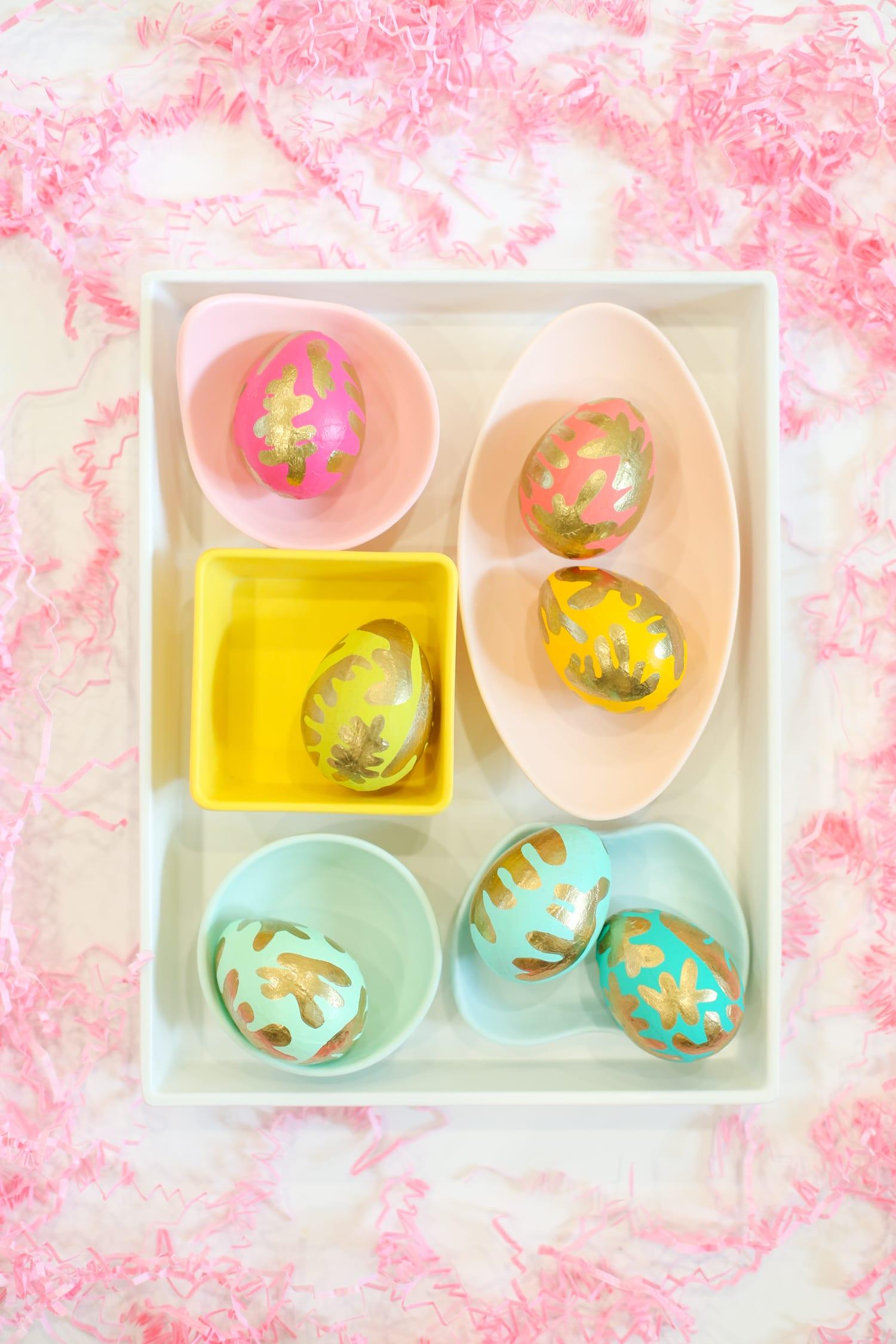 preciosas ideas sobre como pintar huevos de pascua, huevos en colores llamativos con elementos dorados