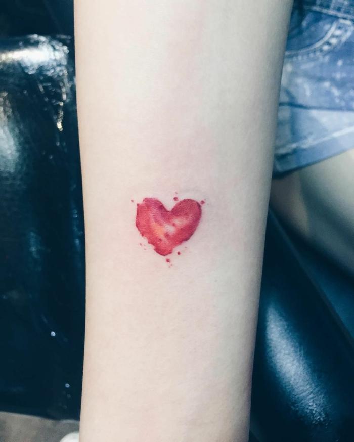 precioso tatuaje en el antebrazo, tatuaje corazon pequeño en color rojo, bonitos diseños de tattoos simbolicos