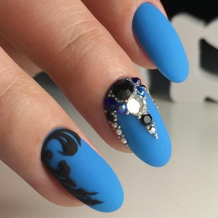 preciosas uñas de forma almendrada pintadas en azul con decoración en negro y cristales brillantes