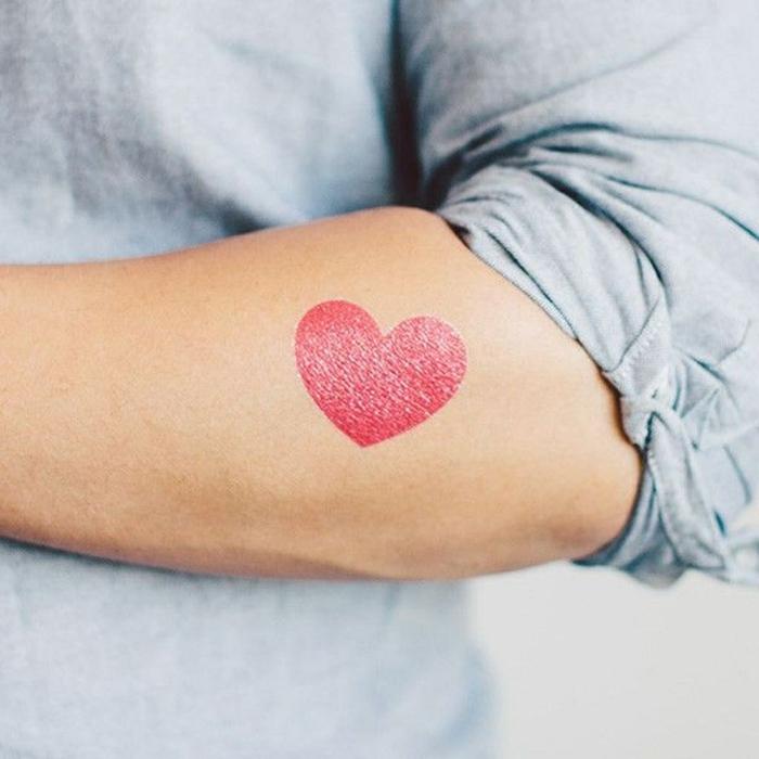precioso tatuaje en el antebrazo en color rojo, diseños de corazon tattoo para hombres y mujeres
