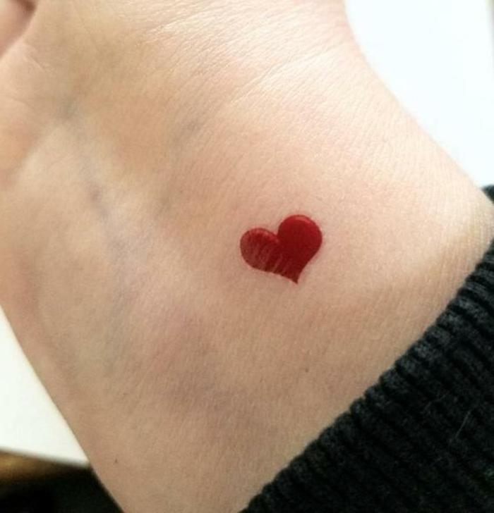 tatuajes minimalistas en la muñeca, pequeño corazón rojo en color rojo, diseños de tatuajes originales