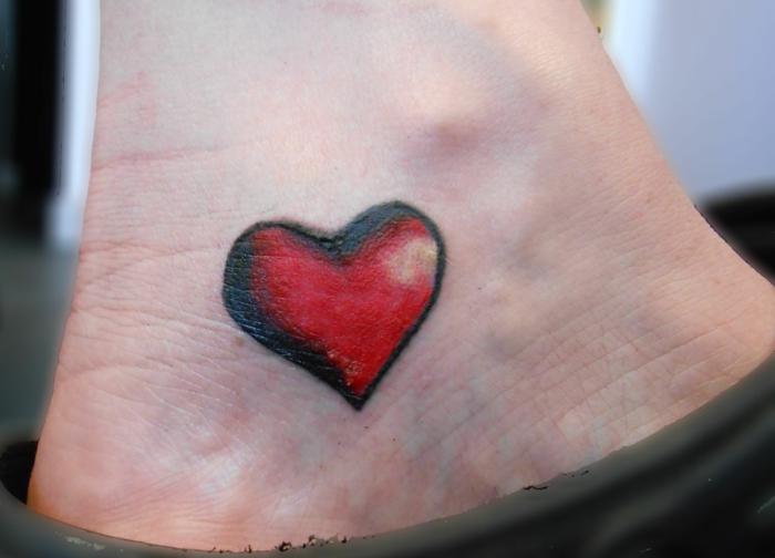 tatuajes pequeños hombre, corazón en rojo y negro tatuado en el tobillo, tattoos simbólicos bonitos