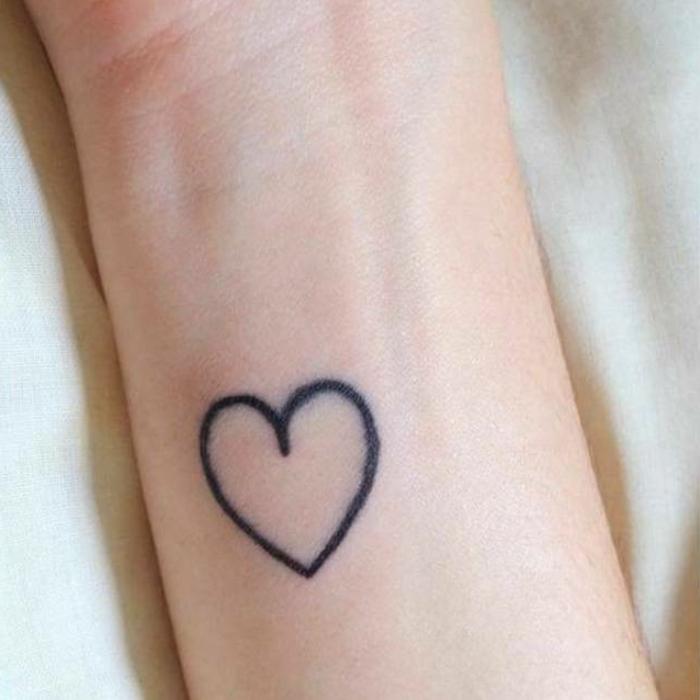 tatuajes pequeños mujer en imagines, pequeño tatuaje corazon en el antebrazo en color negro