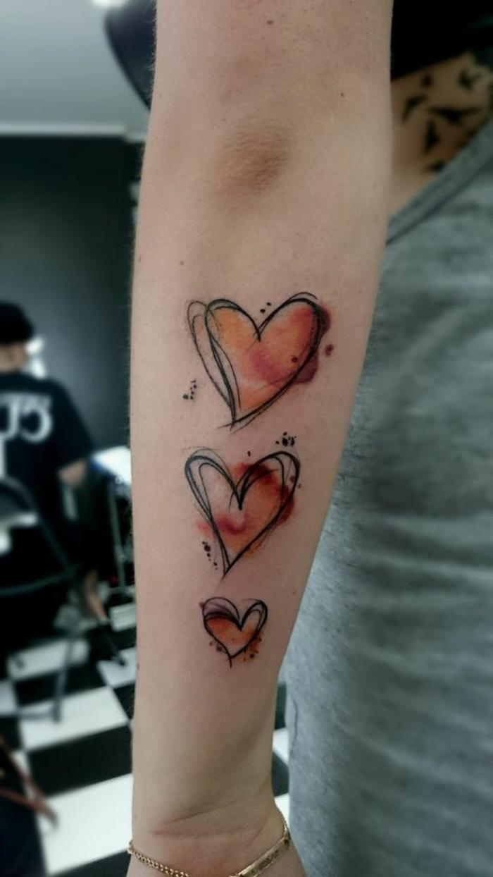 tres corazones de diferente tamaño tatuados en el antebrazo, tatuajes originales con corazón y sus significados