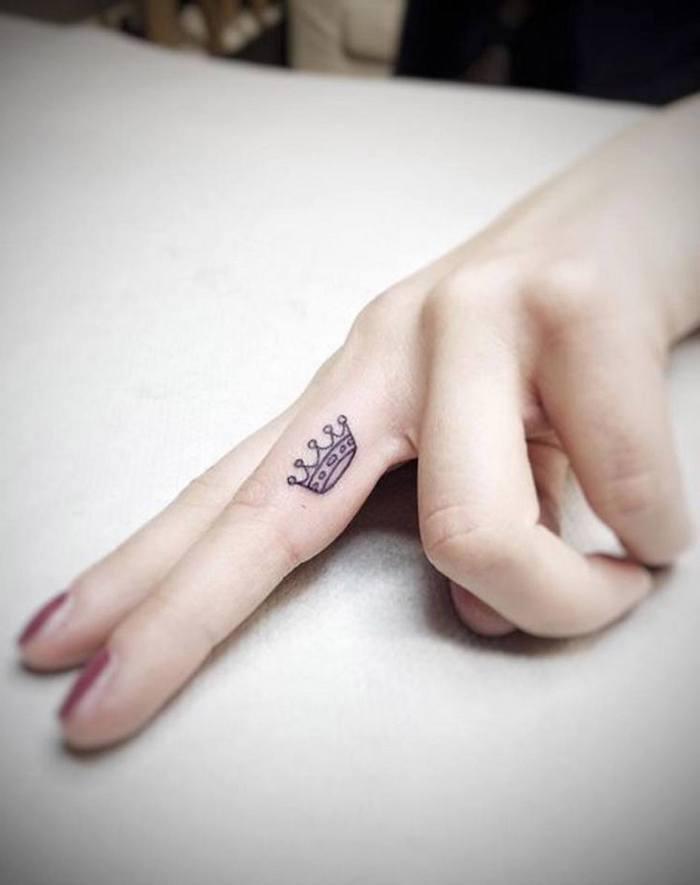mini corona tatuada en el dedo corazón, originales ideas de tatuajes para dedos en imagines
