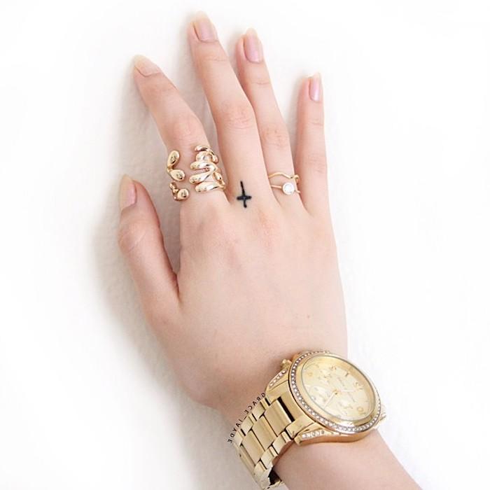 pequeña cruz tatuada en el dedo corazón, ideas de tatuajes para dedos originales en estilo minimalista