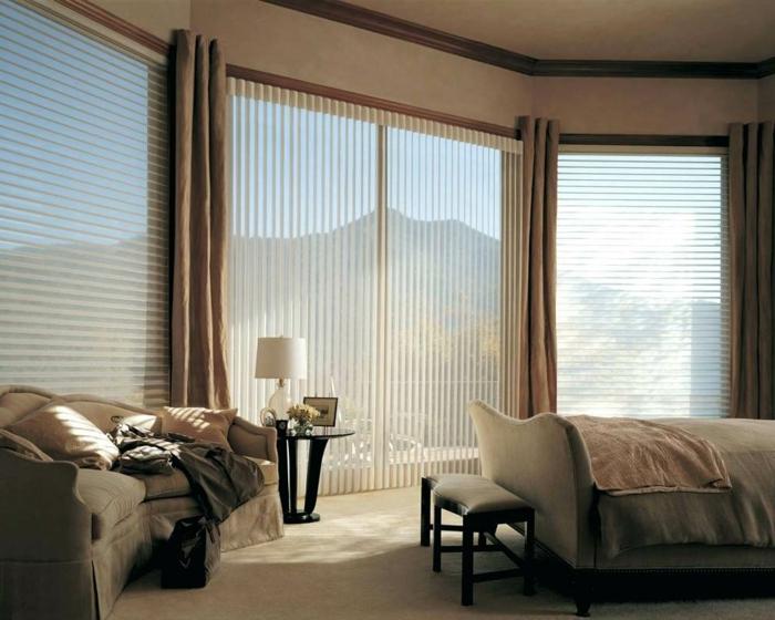habitaciones matrimonio decorada en beige con grandes ventanales, cortinas en beige y suelo de moqueta