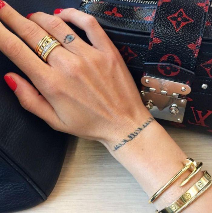 diseños originales de atuajes en los dedos de la mano, pequeño ojo en color azul tatuado en el dedo anular