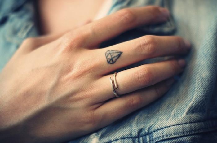 pequeño diamante tatuado en el dedo corazón, las mejores propuestas de tatuajes en los dedos de la mano