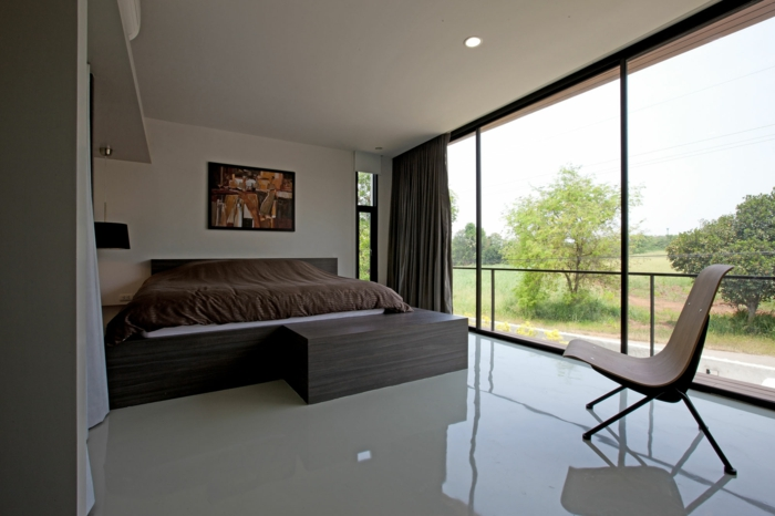 dormitorio en estilo minimalista con grandes ventanales, cama doble, luces empotradas y muebles de diseño