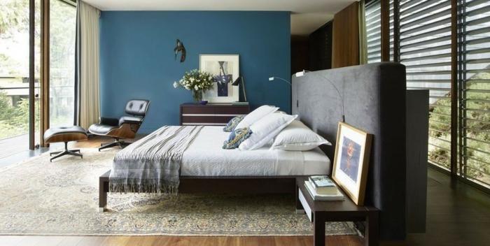 grande habitación decorada con mucho encanto, pared en color azul, cama con cabecero moderno