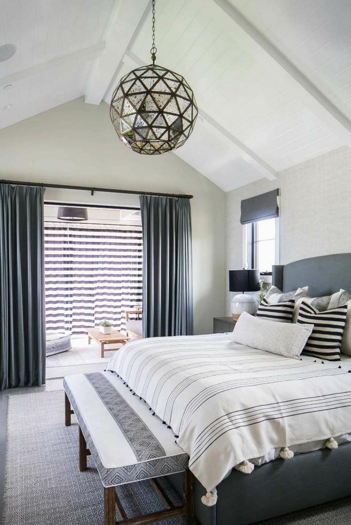 dormitorio decorado en blanco y gris, habitación con techo inclinado, cortinas grises y pie de cama